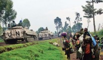 UN armoured vehicles drive past people fleeing renewed fighting between Congolese army and M23 rebels near the eastern Congolese city of Goma