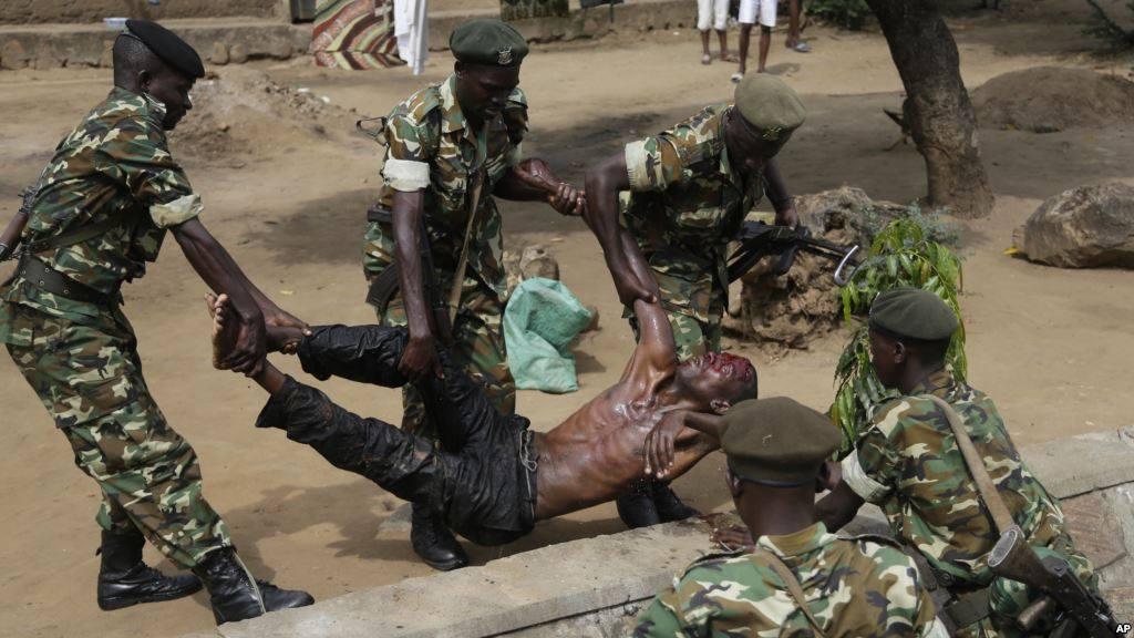 Les forces de l'ordre soulèvent un blessé présumé membre des milices IBONERAKURE attaqué par les manifestants