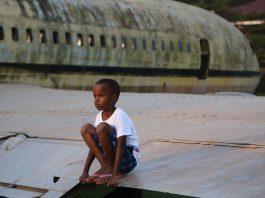 Enfant en Afrique sur un avion abandonné. Crédit photo Thierry Barbaut