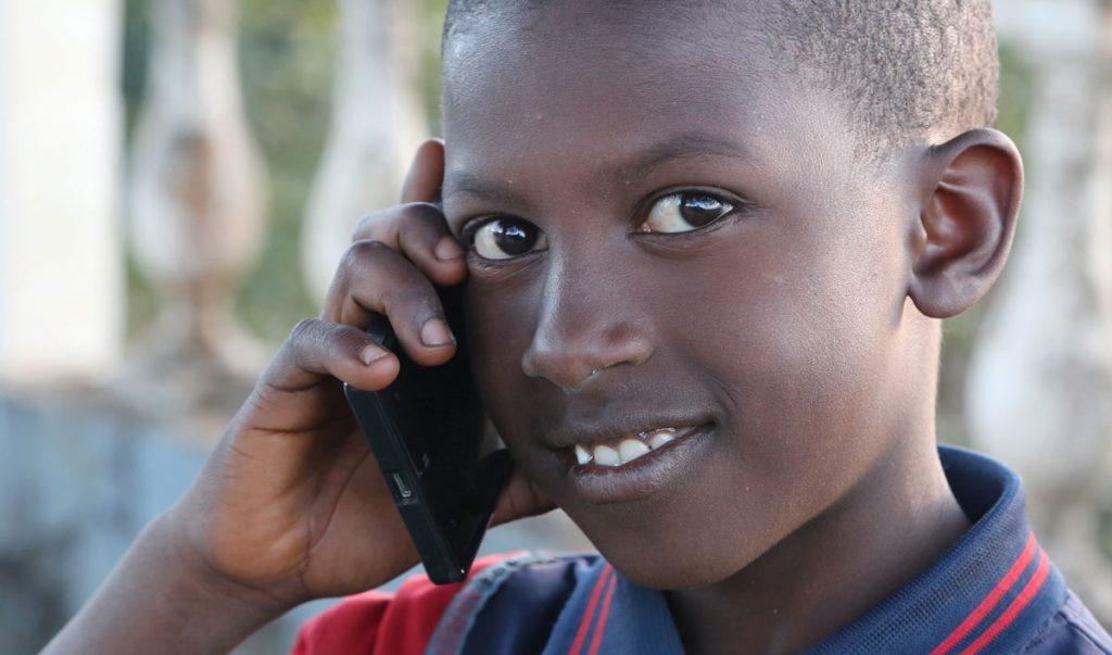 Un enfant au téléphone en Guinée - Crédit photo Thierry BARBAUT